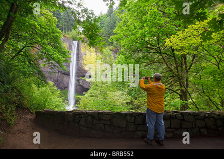 A Hiker Taking A Picture Of Latourell Falls In Columbia River Gorge National Scenic Area; Oregon, United States - Stock Photo