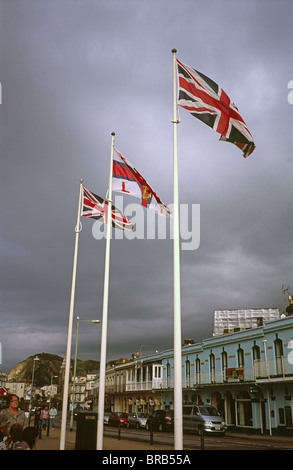 Union Flags and the Royal National Lifeboat Institute flag flying from flagpoles at Ilfracombe seafront, Devon, - Stock Photo