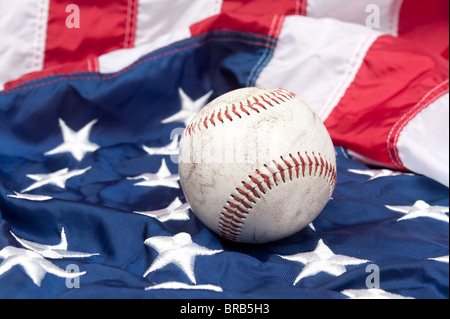 A scuffed up baseball on an American flag. - Stock Photo
