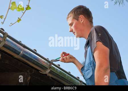 Young plumber fasten a gutter - Stock Photo