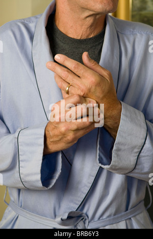 man in bathrobe wringing hands in pain - Stock Photo