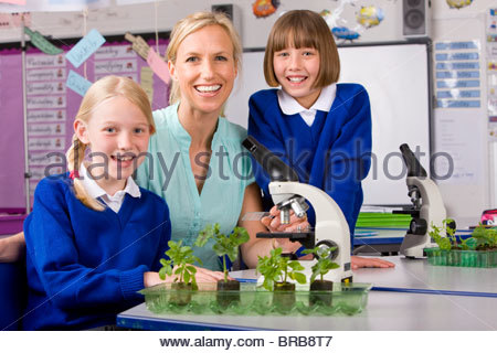 School children and teacher working with microscope in classroom laboratory - Stock Photo