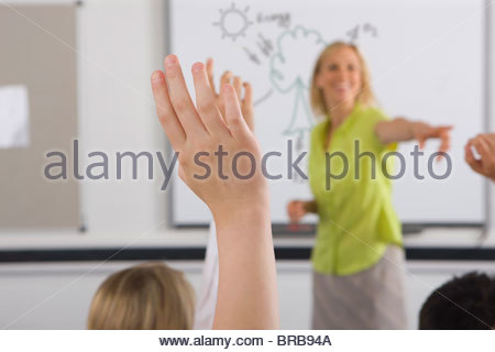 Students answering teacherís questions in classroom - Stock Photo