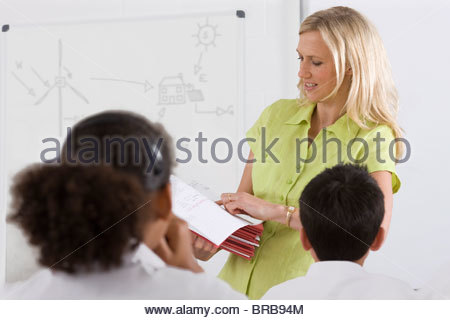 Teacher passing out test booklets to students in classroom - Stock Photo