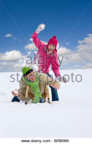 Woman throwing snowball at boyfriend laying on sled - Stock Photo