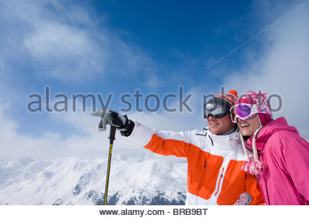 Skier on mountain top pointing out something for friend - Stock Photo