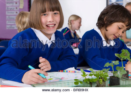 School girl writing in notebook with plant seedlings on desk - Stock Photo