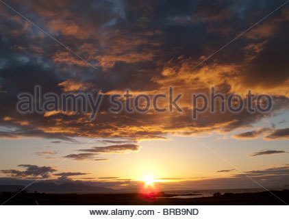 Sunset over land and ocean - Stock Photo