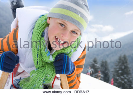 Close up of boy laying on sled on ski slope - Stock Photo