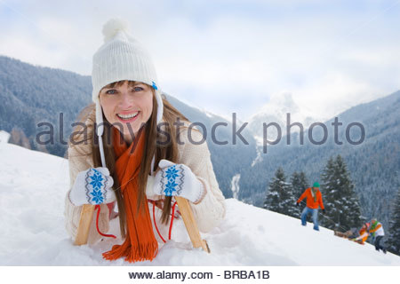 Woman laying on sled on ski slope - Stock Photo