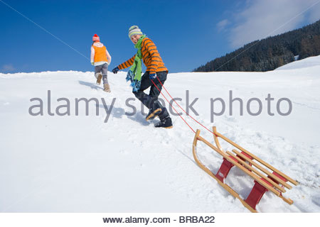 Brother and sister pulling sled up ski slope - Stock Photo