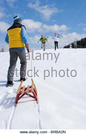 Man pulling sled up hill on ski slope - Stock Photo
