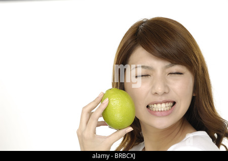 A woman with a lime. The sour flavor of the lime made her make a funny face - Stock Photo
