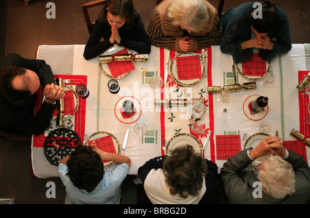 Family prayer before meal, Montrouge, Hauts de Seine, France - Stock Photo
