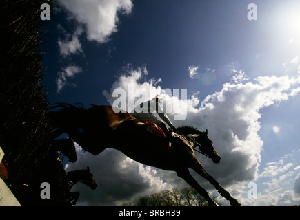 Horses jumping over a fence during a race - Stock Photo