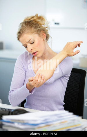 Woman suffering from pains in the elbow - Stock Photo
