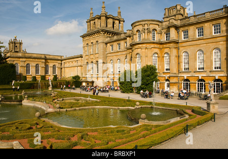 Tourists enjoying the sunshine in the formal gardens at Blenheim Palace, Oxfordshire. - Stock Photo