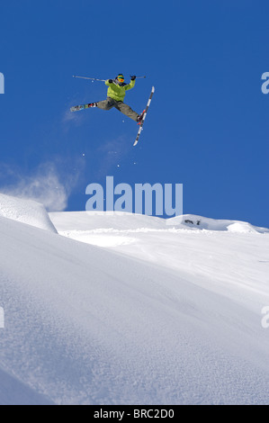 Skier jumps whilst performing an oldschool daffy freestyle trick in the powder snow in Laax, Switzerland - Stock Photo