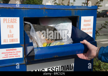Powys Wales UK Woman putting a pair of walking boots into container for recycling footwear no longer of use to walker - Stock Photo