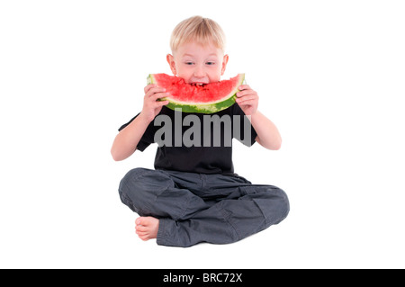 Little boy sitting on the floor taking a big bite from a watermelon - Stock Photo