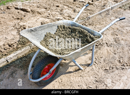 Wheelbarrow with mortar on road construction - Stock Photo