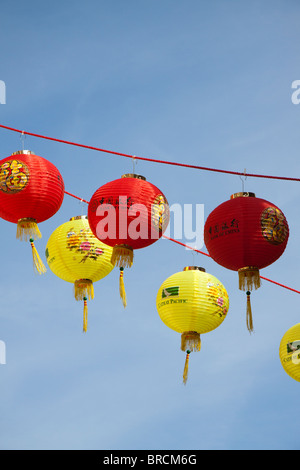 Red and yellow Chinese lanterns hanging against a blue sky - Stock Photo