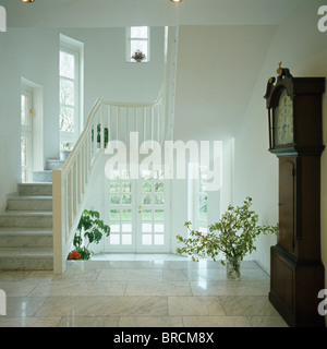Antique long-case clock in light and airy modern white hall with marble tiled floor - Stock Photo