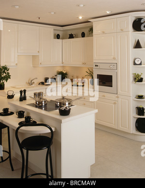 White Stools At Breakfast Bar On Island Unit In Modern