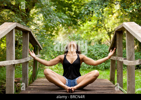 athletic woman in short jean practicing relaxation in nature - Stock Photo