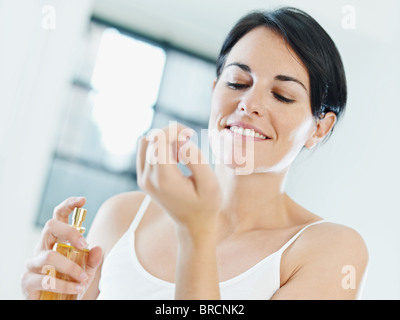 woman applying perfume on wrist - Stock Photo