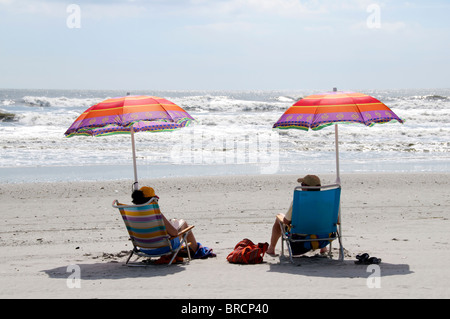 Mature couple relaxing on the beach sitting under colorful umbrellas. - Stock Photo