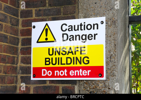 Warning sign for unsafe building - Stock Photo