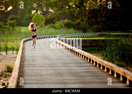 Running girl on a wooden bridge - Stock Photo