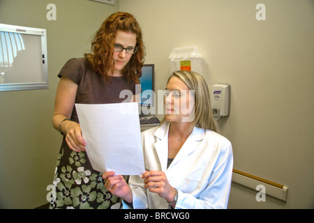 A doctor and her patient read a document of mutual interest at a Newport Beach, CA, medical clinic. MODEL RELEASE - Stock Photo