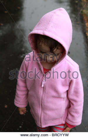 A 2 year old girl standing in the rain and wearing a pink hoodie. - Stock Photo