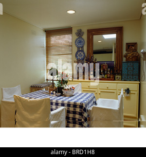 White Loose Covers On Chairs At Table With Blue Checked Cloth In Small Dining Room
