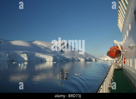 Cruise ship with lifeboat, mountains & glaciers reflected in calm ocean, Paradise harbor, Antarctica  - Stock Photo