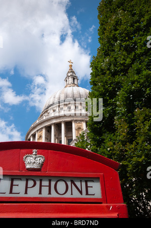A red London phone box seen in the foreground with St Paul's Cathedral at the back. - Stock Photo