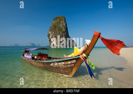 Woman relaxing on a long-tail boat at Laem Phra Nang Beach, Krabi, Thailand - Stock Photo