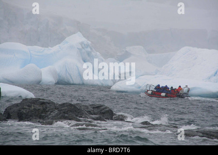 Tourists in zodiac offshore among icebergs, Cuverville Island, Antarctica