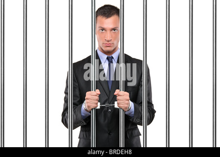 A handcuffed businessman in jail holding bars - Stock Photo