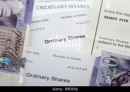 ordinary share certificates with twenty pound notes in the uk - Stock Photo