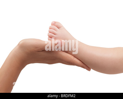 Mother holding her three month old baby son's foot in her hands. Isolated on white background with a clipping path. - Stock Photo
