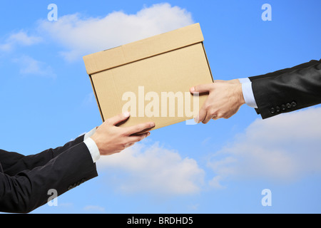 A businessman delivering a package to a man - Stock Photo