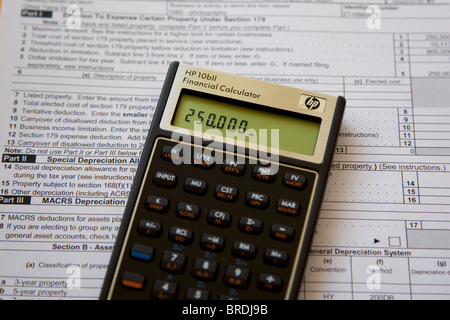 Calculator calculating income taxes on tax form, expenses and income Stock Photo