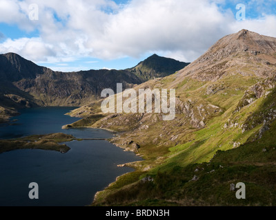 The shapely cone of Crib Goch rises above the lake of Llyn Llydaw, with Yr Wyddfa, the summit of Snowdon, in view behind.