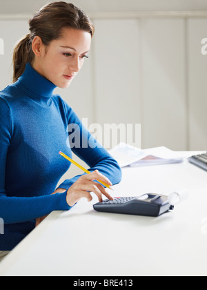 woman using calculator in office - Stock Photo
