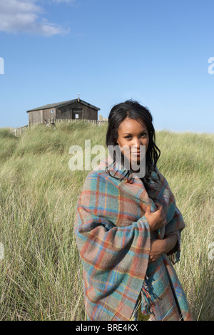 Young Woman Standing On Beach Wrapped In Blanket With Beach Hut In Distance - Stock Photo