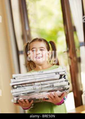 girl carrying newspapers for recycling, looking at camera, copy space - Stock Photo