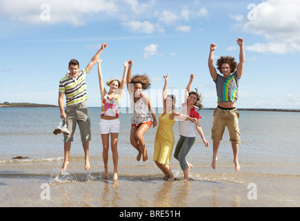 Group Of Teenage Friends Having Fun On Beach Together Jumping In Air - Stock Photo